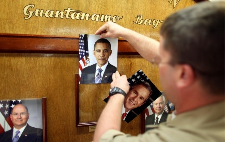 U.S. Navy Chief Petty Officer Bill Mesta replaces an official picture of outgoing President George W. Bush with that of newly-sworn-in U.S. President Barack Obama, in the lobby of the headquarters of the U.S. Naval Base January 20, 2009 in Guantanamo Bay, Cuba. (Brennan Linsley-Pool/Getty Images)